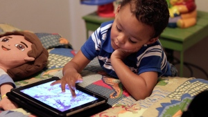 A three-year-old plays with an iPad