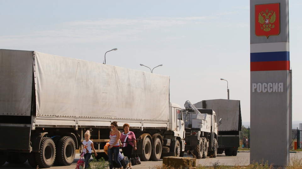 Trucks marked as being from a bitterly disputed Russian aid convoy to Ukraine, stand in line as they return to Russia in the Russian town of Donetsk, Rostov-on-Don region, Russia, Saturday, Aug. 23, 2014. (AP / Sergei Grits)