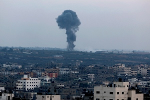 Smoke and dust rise after an Israeli strike hits Gaza City in the northern Gaza Strip, Friday, Aug. 22, 2014. Senior Hamas officials say the group has signed a written pledge supporting a Palestinian bid to join the International Criminal Court. (AP Photo/Adel Hana)