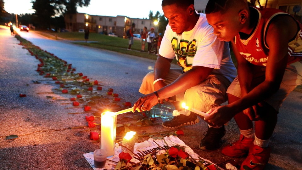 Theo Murphy, left, of Florissant, Mo., and his brother Jordan Marshall, 11, light candles at a memorial on Canfield Drive in Ferguson, Mo., Thursday, Aug. 21, 2014. (AP / St. Louis Post-Dispatch, Christian Gooden)