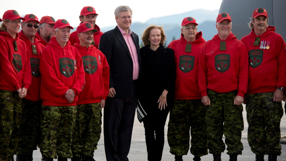 Prime Minister Stephen Harper and wife Laureen pose for a photograph with Canadian Rangers as they leave Whitehorse on Friday, Aug. 22, 2014. (Adrian Wyld / THE CANADIAN PRESS)