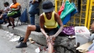 In this photo taken Feb. 15, 2011, a woman applies skin lightening cream to her legs as she sits on a curb in Kingston, Jamaica. People around the world often try to alter their skin color, using tanning salons or dyes to darken it or other chemicals to lighten it. (AP/Caterina Werner)