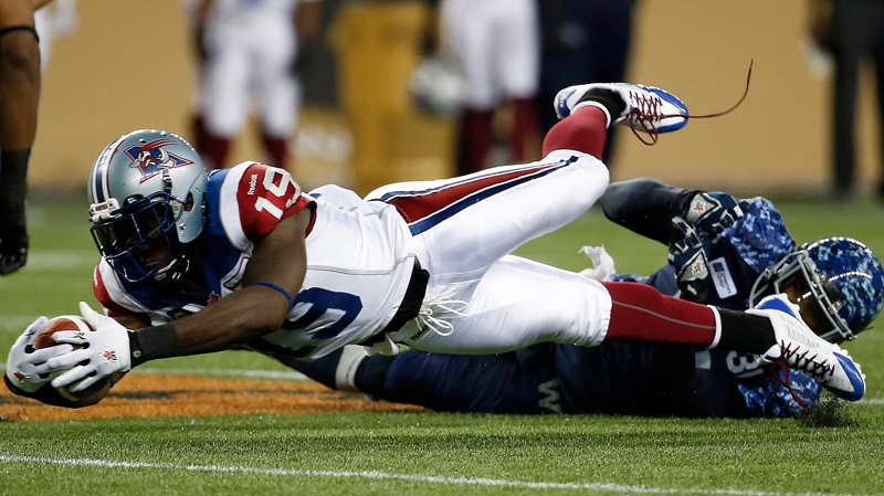 Montreal Alouettes' S.J. Green (19) dives for extra yards against Winnipeg Blue Bombers' Maurice Leggett (31) during the second half of CFL action in Winnipeg Friday, August 22, 2014. THE CANADIAN PRESS/John Woods