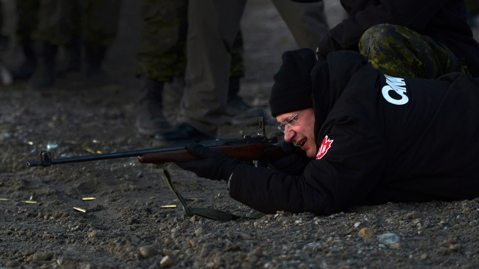Prime Minister Stephen Harper shoots .303 Lee Enfield rifle in Gjoa Haven, Nunavut on Tuesday, August 20, 2013. (THE CANADIAN PRESS / Sean Kilpatrick)