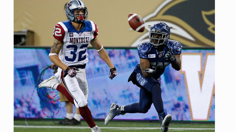 Winnipeg Blue Bombers' Clarence Denmark (89) snags a pass in front of Montreal Alouettes' Mitchell White (32) during the second half of CFL action in Winnipeg Friday, August 22, 2014. THE CANADIAN PRESS/John Woods