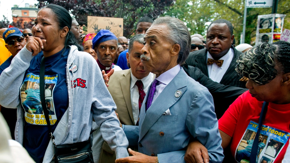 Esaw Garner, left, arrives with the Rev. Al Sharpton, centre, at the spot where her husband Eric Garner died in the Staten Island borough of New York, Saturday, Aug. 23, 2014. (AP / Craig Ruttle)