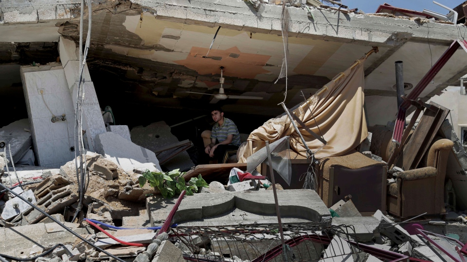 A Palestinian sits amid the rubble of a three-story building that belongs to the Abu Akleen family after it was destroyed in an Israeli strike late Friday, in the Sabra neighborhood of Gaza City in the northern Gaza Strip, Saturday, Aug. 23, 2014. (AP / Adel Hana)