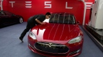 A worker cleans a Tesla Model S sedan in Beijing on April 22, 2014. (AP / Ng Han Guan)