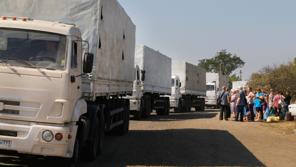 Trucks marked as being from a bitterly disputed Russian aid convoy to Ukraine stand in line as they return to Russia on the border post at Izvaryne, eastern Ukraine, Saturday, Aug. 23, 2014. (AP / Sergei Grits)