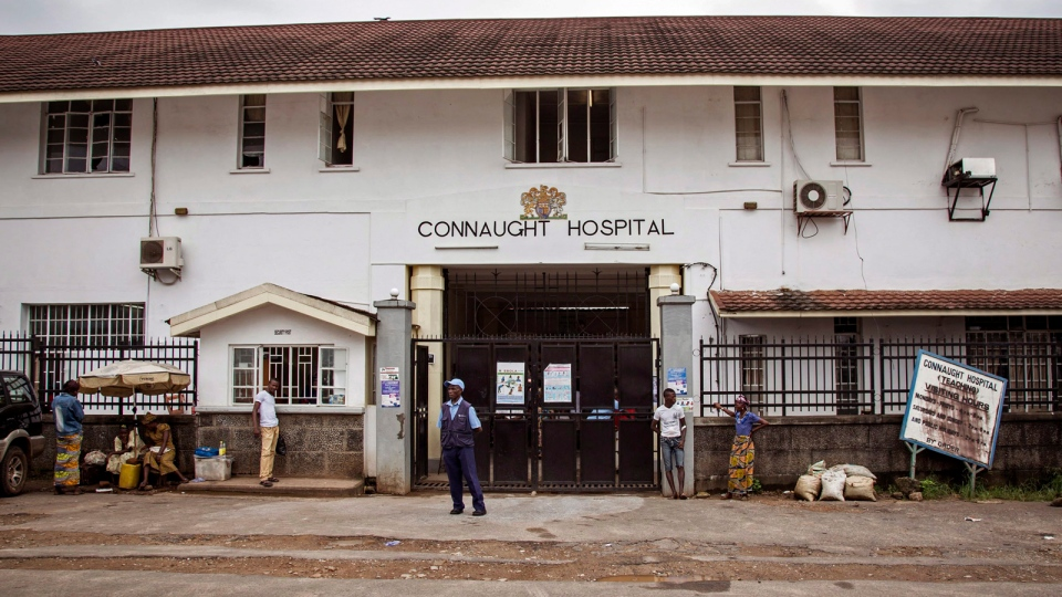 A security guard, center, stands outside the Connaught Hospital, where a leading doctor died from Ebola on Wednesday, in Freetown, Sierra Leone, Friday, Aug. 15, 2014. (AP / Michael Duff)