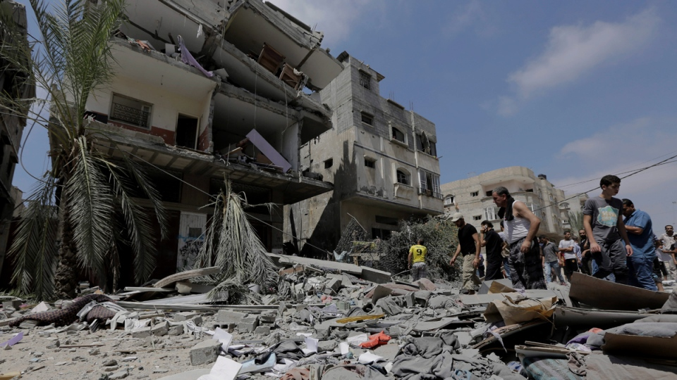 Palestinian relatives salvage belongings from the rubble of a three-storey building in Gaza City on Aug. 24, 2014. (AP / Adel Hana)