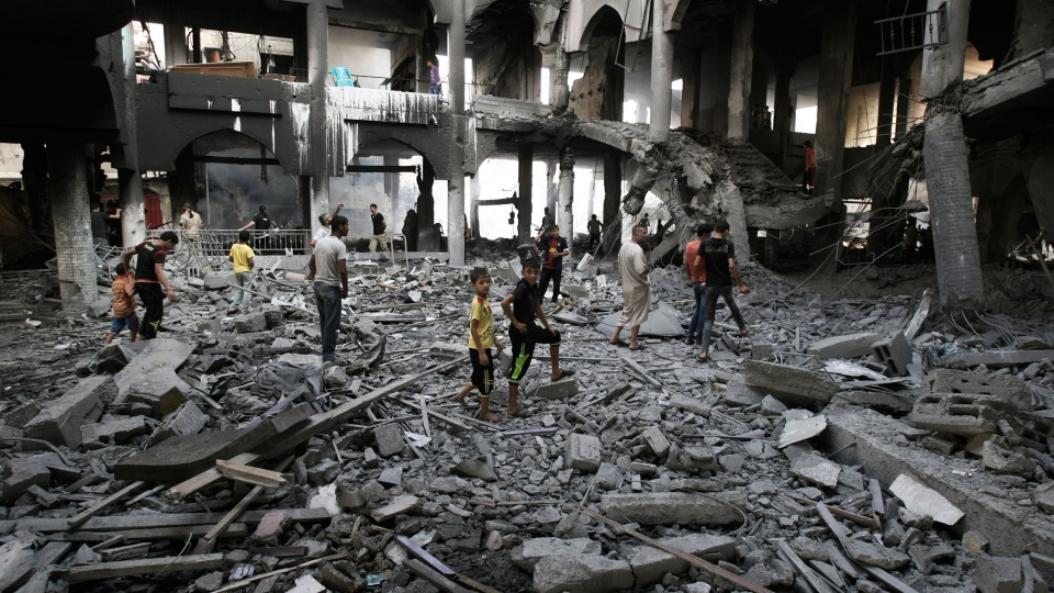 Palestinians inspect the damage of a Rafah commercial center after an Israeli strike in Rafah, in the southern Gaza Strip, Sunday, Aug. 24, 2014. (AP / Eyad Baba)