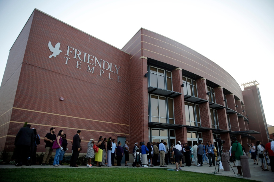 People begin to line up to attend the funeral for Michael Brown, Monday, Aug. 25, 2014, in St. Louis. (AP Photo/Jeff Roberson)
