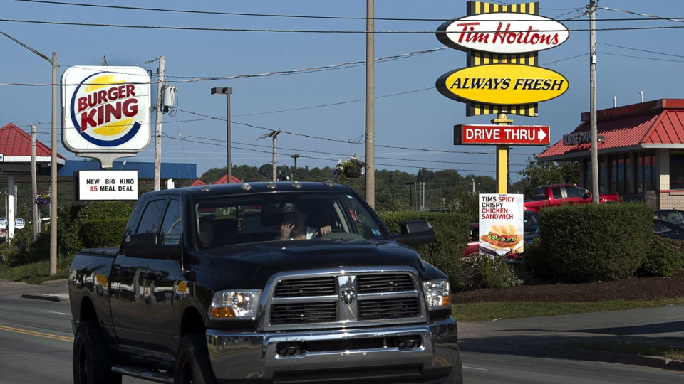 A Tim Hortons restaurant is seen located next to a Burger King restaurant in Lower Sackville, N.S. on Monday, Aug. 25, 2014. (Andrew Vaughan / THE CANADIAN PRESS)