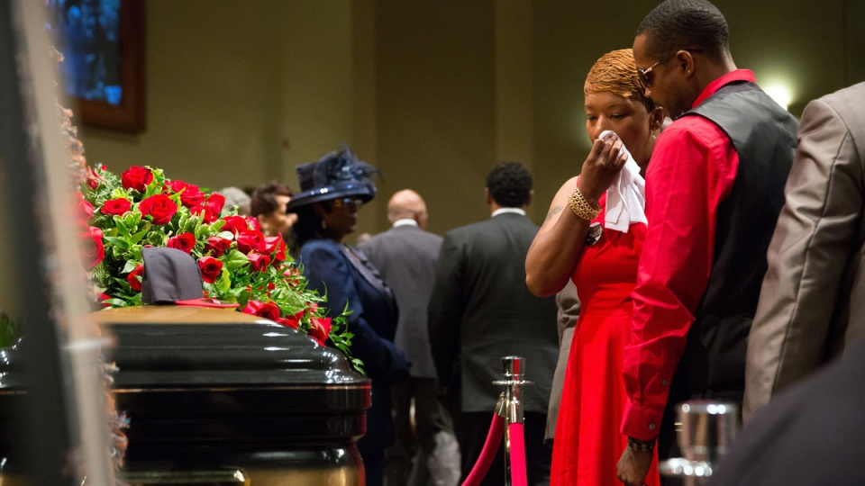 Lesley McSpadden, mother of Michael Brown, wipes a tear as she stands by his casket at his the funeral at Friendly Temple Missionary Baptist Church in St. Louis, Monday, Aug. 25, 2014. (AP / New York Times, Richard Perry)