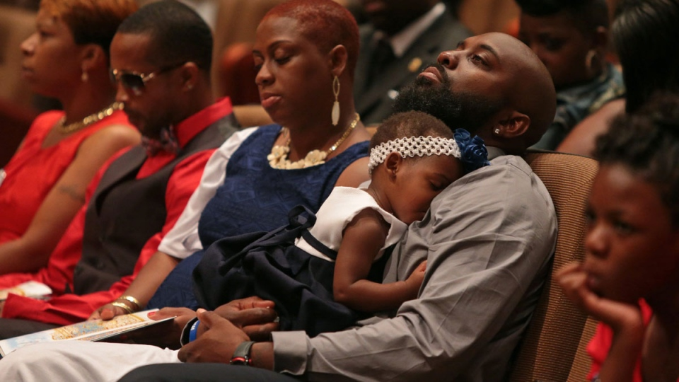 Michael Brown Sr. sits with an unidentified girl on his lap during the funeral services for his son Michael Brown, at Friendly Temple Missionary Baptist Church in St. Louis on Monday, Aug. 25, 2014. (AP / St. Louis Post Dispatch, Robert Cohen)