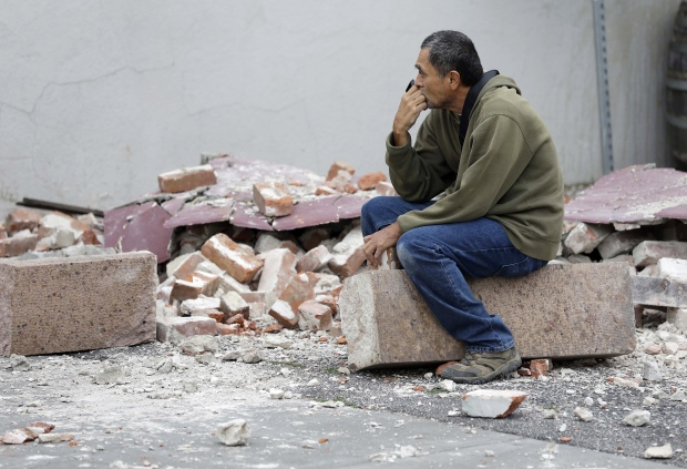 Ron Peralez, of Vacaville, Calif., sits on rubble and looks at earthquake-damaged buildings, in Napa, Calif., Monday, Aug. 25, 2014. (AP / Eric Risberg)