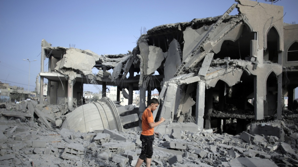 A Palestinian walks amid the rubble of the Omar Ibn Abdul Aziz mosque after it was hit by an Israeli strike in Gaza City, Monday, Aug. 25, 2014. (AP / Khalil Hamra)