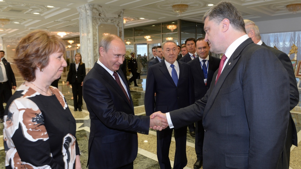Russian President Vladimir Putin, second left, shakes hands with Ukrainian President Petro Poroshenko, right, as EU foreign policy chief Catherine Ashton, left, and Kazakh President Nursultan Nazarbayev, center, watch, prior to their talks after after posing for a photo in Minsk, Belarus, Tuesday, Aug. 26, 2014.  (Sergei Bondarenko / Kazakh Presidential Press Service)