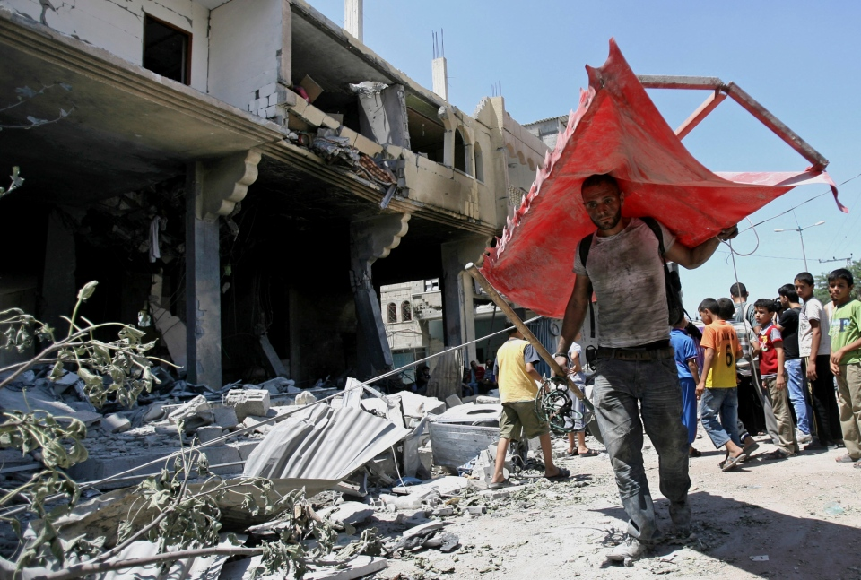 A Palestinian relative salvages what he can from his family's belongings amid the rubble of the al-Akhras family home after it was hit by Israeli strike in Rafah refugee camp, southern Gaza Strip, Tuesday, Aug. 26, 2014. (AP / Eyad Baba)
