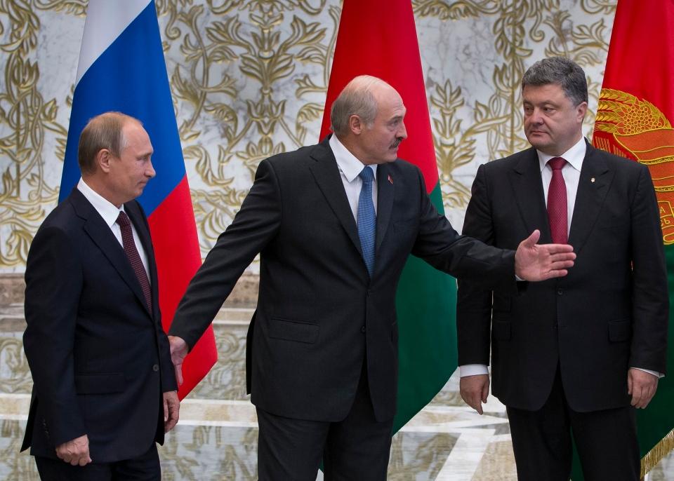 Belarusian President Alexander Lukashenko, centre, welcomes Russian President Vladimir Putin, left, and Ukrainian President Petro Poroshenko, right, to their talks after posing for a photo in Minsk, Belarus, Tuesday, Aug. 26, 2014.  (AP / Alexander Zemlianichenko)