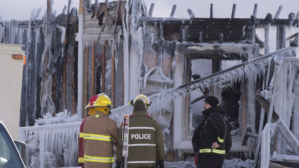 Police and firefighters survey the damage after a fatal fire at a seniors' residence in L'Isle-Verte, Que., Thursday, Jan. 23, 2014. (Jacques Boissinot / THE CANADIAN PRESS)