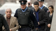 Mohammad Shafia, front, Tooba Yahya, back, and their son Hamed Shafia, middle, are escorted into the Frontenac County courthouse in Kingston, Ont., Friday, Jan. 27, 2012. (Frank Gunn / THE CANADIAN PRESS)