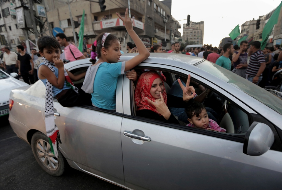 A Palestinian family flashes victory signs as they celebrate the cease-fire between Palestinians and Israelis at the main road in Gaza, in the northern Gaza Strip, Tuesday, Aug. 26, 2014. (AP / Adel Hana)