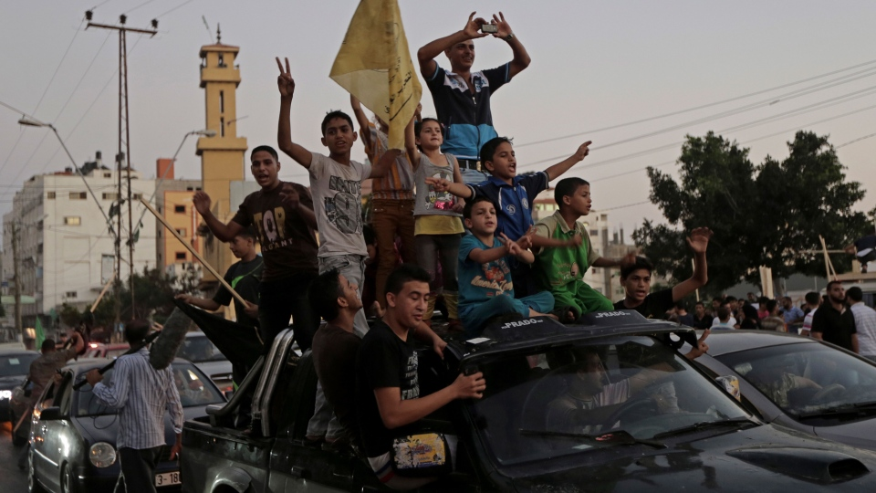 Palestinians celebrate the cease-fire between Palestinians and Israelis at the main road in Gaza, in the northern Gaza Strip, Tuesday, Aug. 26, 2014. (AP / Adel Hana)