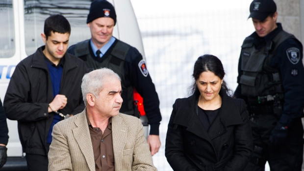 Mohammad Shafia, front left, Tooba Yahya, front right, and their son Hamed Shafia, back left, are escorted at the Frontenac County courthouse in Kingston, Ontario on Saturday, January 28, 2012.