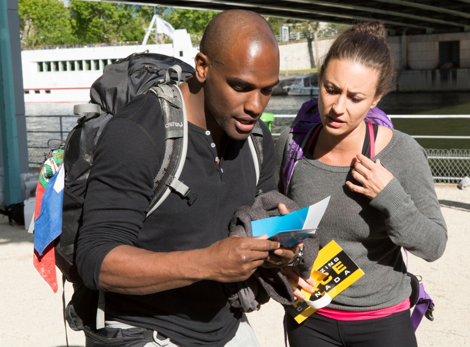 Alain and Audrey read their clue in an episode of Amazing Race Canada filmed in Paris.