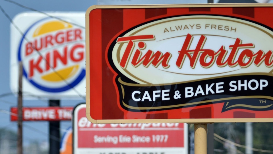 Signs for a Tim Hortons restaurant, foreground, and a Burger King restaurant are displayed along Peach Street in Erie, Penn., Tuesday, Aug. 26, 2014. (AP / Erie Times-News, Christopher Millette)