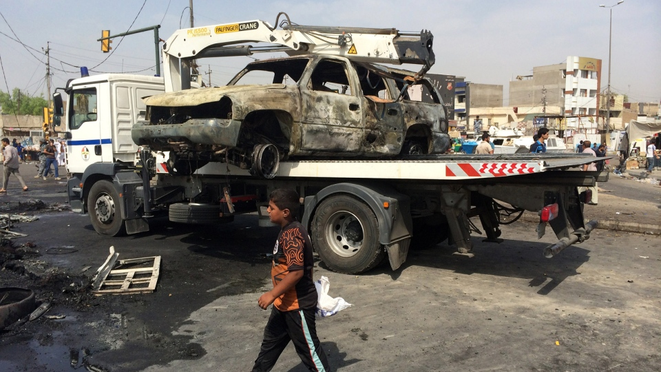 A tow truck remove a vehicle from the site of a car bomb explosion in a commercial area of New Baghdad, Iraq, Tuesday, Aug. 26, 2014. (AP / Khalid Mohammed)
