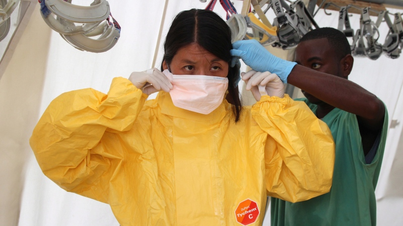 Dr. Joanne Liu, international president of Medecins Sans Frontieres (Doctors Without Borders) puts on a mask as she visits the Ebola treatment centre in Kailahun, Sierra Leone in this recent handout photo.  (P.K. Lee / Medecins Sans Frontieres / THE CANADIAN PRESS)