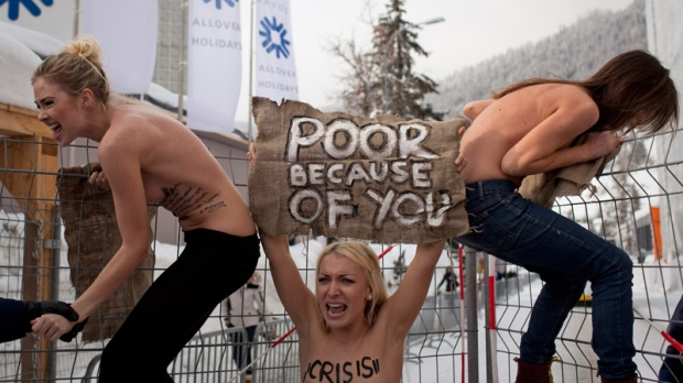 Topless Ukrainian protesters climb up a fence at the entrance to the congress center where the World Economic Forum takes place in Davos, Switzerland Saturday, Jan. 28, 2012.