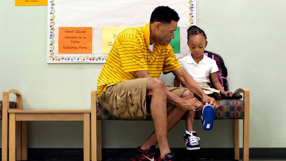 Claude Victor helps his daughter, Haleisha Victor, get ready for her first day of kindergarten at Parkside Elementary School in Naples, Fla. on Aug. 18, 2014. (AP / Naples Daily News, Carolina Hidalgo)