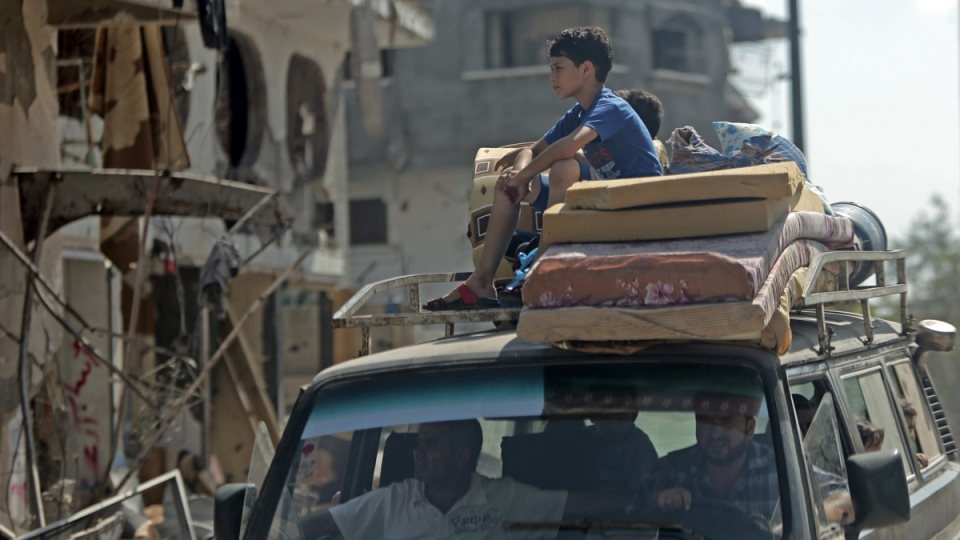 Palestinians with their belongings drive back to their homes in Gaza City's Shijaiyah neighborhood, Wednesday, Aug. 27, 2014. (AP / Khalil Hamra)