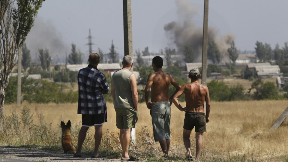 Local residents watch as smoke rises, during shelling, in the town of Novoazovsk, eastern Ukraine, Wednesday, Aug. 27, 2014. (AP / Sergei Grits)