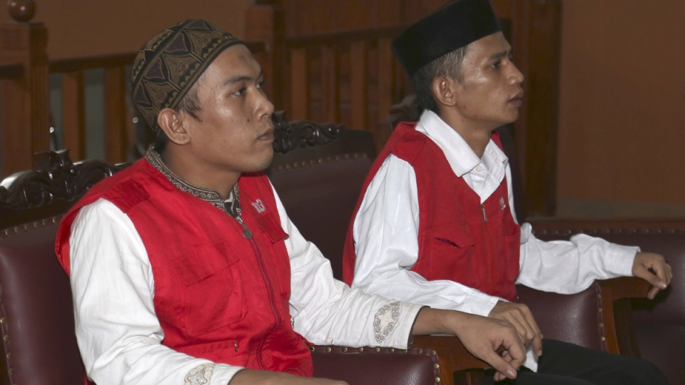 Child sexual abuse suspects Syahrial, left, and Zainal Abidin sit on the defendant's chairs at the start of their trial at South Jakarta District Court in Jakarta, Indonesia, Wednesday, Aug. 27, 2014. (AP / Tatan Syuflana)