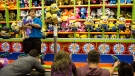 Visitors play a game at a booth at the Canadian National Exhibition in Toronto on Saturday, Aug. 23, 2014. (Chris Young / THE CANADIAN PRESS)