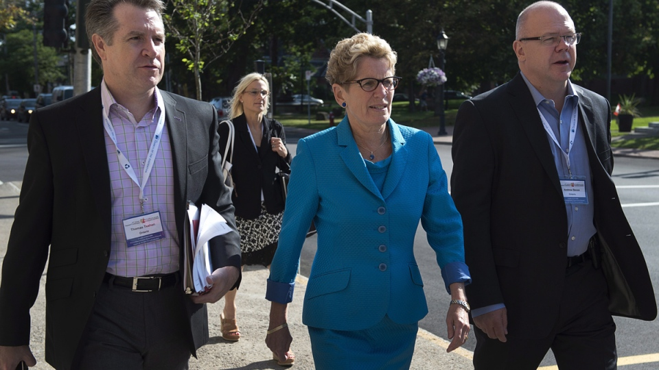 Ontario Premier Kathleen Wynne is flanked by Thomas Teahen, left, chief of staff and Andrew Bevan, right, principal secretary, as she heads to a meeting of premiers and aboriginal leaders in Charlottetown on Wednesday, Aug. 27, 2014. (Andrew Vaughan / THE CANADIAN PRESS)