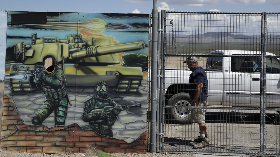 A man closes off an entrance to the Last Stop outdoor shooting range, in White Hills, Ariz., Wednesday, Aug. 27, 2014. (AP / John Locher)