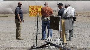 People are seen at the Last Stop outdoor shooting range, in White Hills, Ariz., Wednesday, Aug. 27, 2014. (AP / John Locher)