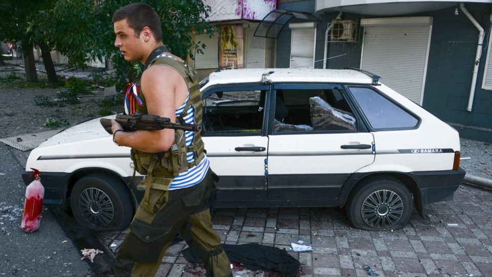A Pro-Russian rebel passes by a car which was hit by shrapnel from a shell after shelling in the town of Donetsk, eastern Ukraine, Wednesday, Aug. 27, 2014. (AP / Mstislav Chernov)
