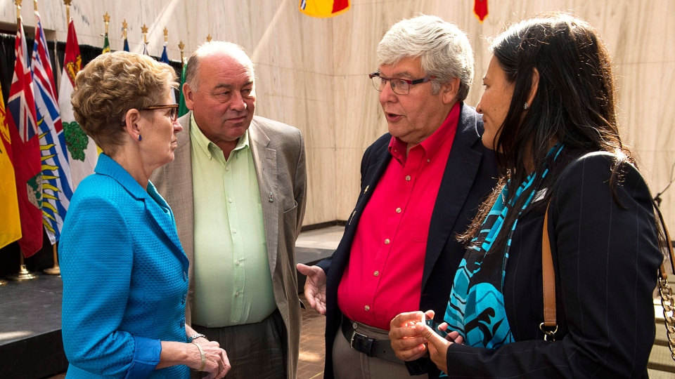 Ontario Premier Kathleen Wynne, Northwest Territories Premier Bob McLeod, Alberta Premier Dave Hancock and Michele Audette, president of the Native Women's Association of Canada, left to right, chat after a meeting of premiers and aboriginal leaders in Charlottetown on Wednesday, August 27, 2014. (Andrew Vaughan / THE CANADIAN PRESS)