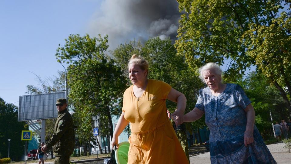 Women rush across the street after shelling in the town of Donetsk, eastern Ukraine, Wednesday, Aug. 27, 2014. (AP / Mstislav Chernov)