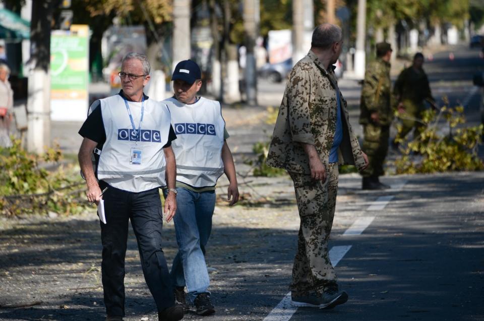 Members of the OSCE examine the scene of a shelling in the town of Donetsk, eastern Ukraine, Wednesday, Aug. 27, 2014. (AP / Mstislav Chernov)