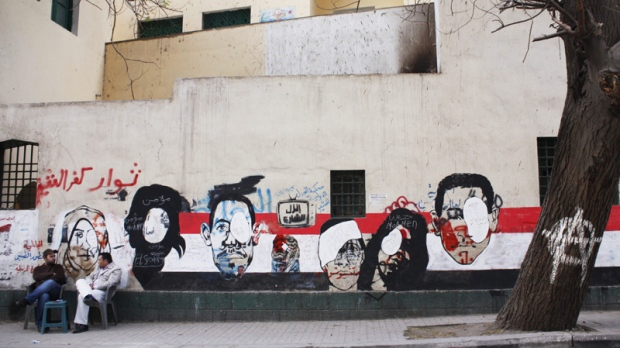 In this Saturday, Dec. 24, 2011 photo, men sit near revolutionary murals depicting those who lost their eyes during clashes near Tahrir Square in Cairo, Egypt.