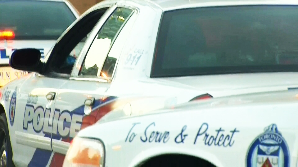 Police cars are parked outside of a station after a series of early morning raids in Toronto, Thursday, Aug. 28, 2014.