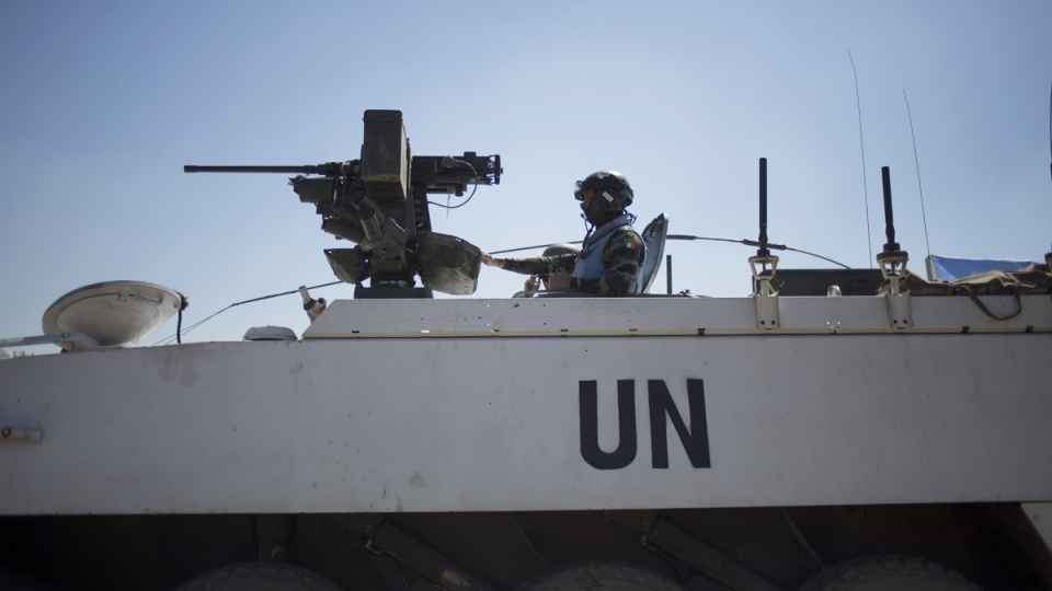 Armored vehicles from the UN peacekeepers of the United Nations Disengagement Observer Force, also known as UNDOF wait to cross from the Israeli controlled Golan Heights to Syria, Thursday, Aug. 28, 2014. (AP / Ariel Schalit)